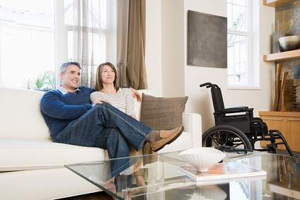 A couple sitting in a living room, a wheelchair in the background